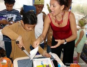 Onder toeziend oog van zijn moeder Jackeline snijdt Lennon de taart aan voor zijn tiende verjaardag. Klik voor groter!