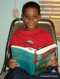 Luchiano (9) met CasaSpiders bril op heeft het boek