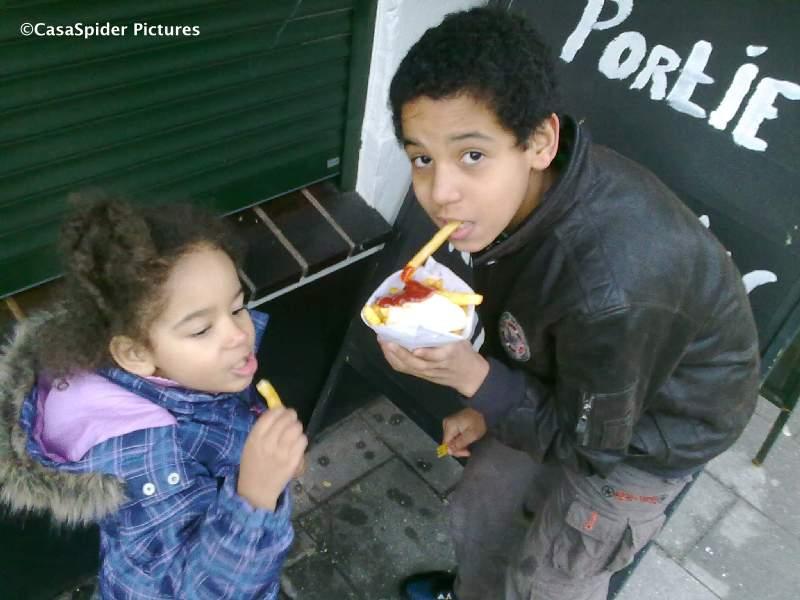 24.01.2010: Diana (3) en Luchiano (12) smullen van de Belgische frieten in Baarle Hertog / Baarle Nassau. Klik voor groter.