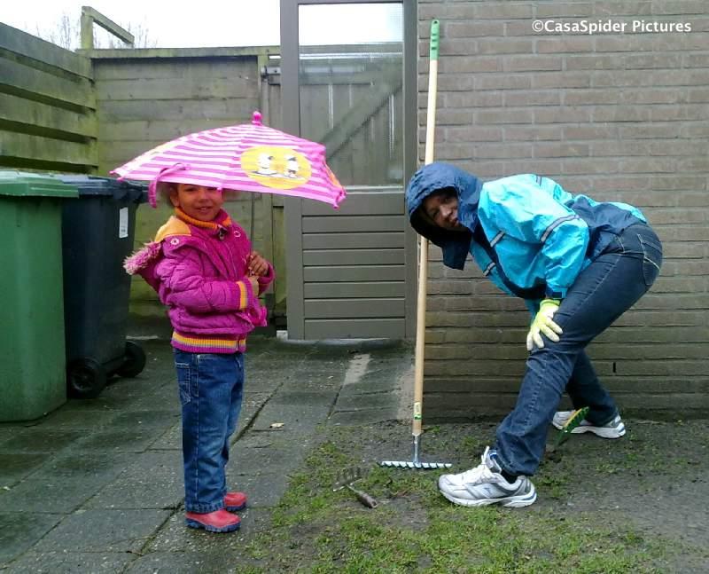 21.03.2010: Lucy en Diana planten de bij GardenMaster Rijen gekochte plantjes, ook al regent het. Klik voor groter.
